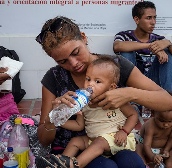 Newly arrived Venezuelan refugees and migrants rest by a Red Cross Information Point