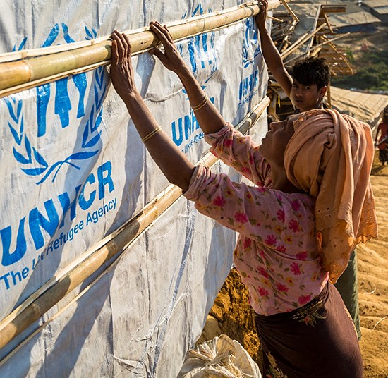 A women reinforces her shelter with materials provided by UNHCR.