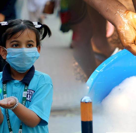 Young girl wearing a mask is given hand sanitiser to help protect her against COVID-19