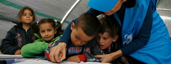 UNHCR worker assists four young children in the classroom