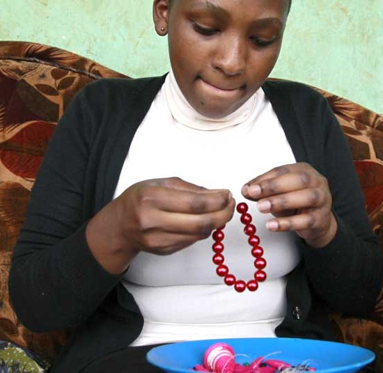 A young woman makes works on her keyrings as part of the 'Keyring Project' in Kampala, Uganda