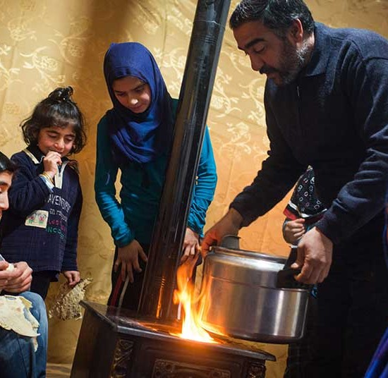 A Syrian refugee family in Lebanon gather around their stove for warmth | Winter Survival Fund Appeal