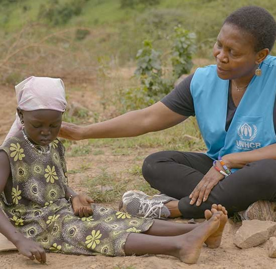 Mmone Moletsane is a Child Protection Officer for UNHCR in Ethiopia with a child | Forgotten Childhoods appeal
