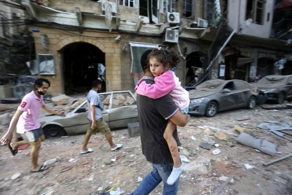 Man carries child through rubble in the aftermath of the Beirut blast that tore through Lebanon's capital.