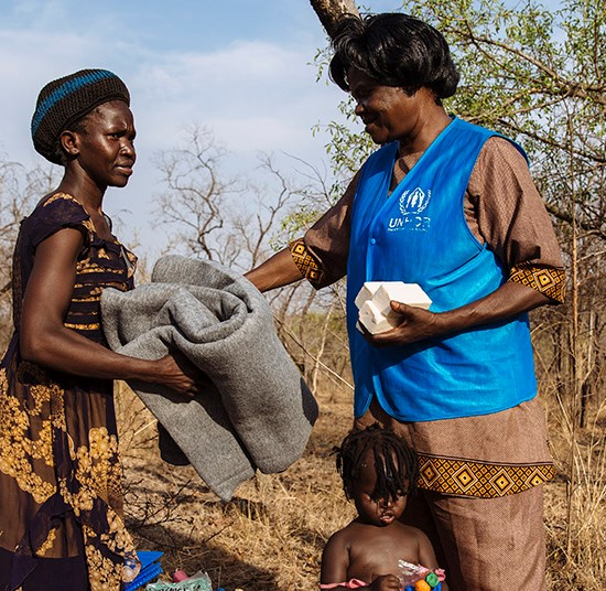 A mother and child are provided with soap and blankets by a UNHCR field worker | South Sudan emergency