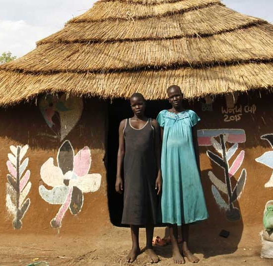 Nyakong and her daughter outside the hut they built in an Ethiopian camp