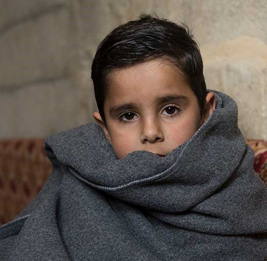 Mohammad keeps warm inside a blanket provided by UNHCR | Winter Survival Fund