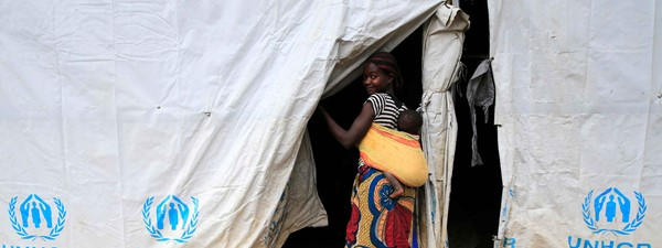 Woman carries baby in a swaddle into a UNHCR tent