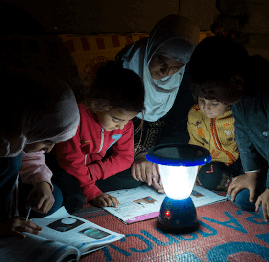 Woman and four children read under a solar lamp