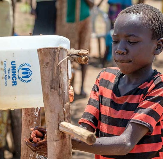 "A young South Sudanese refugee washes his hands using a ""tip-it-tap"" at Bidibidi refugee settlement in Uganda. 