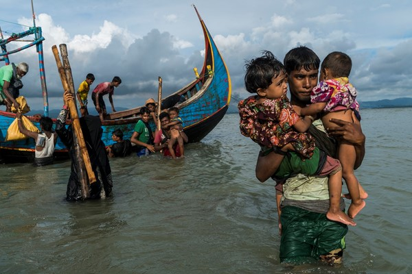 Rohingya refugees wade through water, fleeing Myanmar