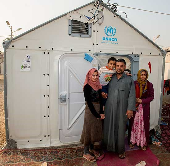 A family gather outside their durable housing unit, glad for the shelter in the winter months | Winter Survival Fund Appeal