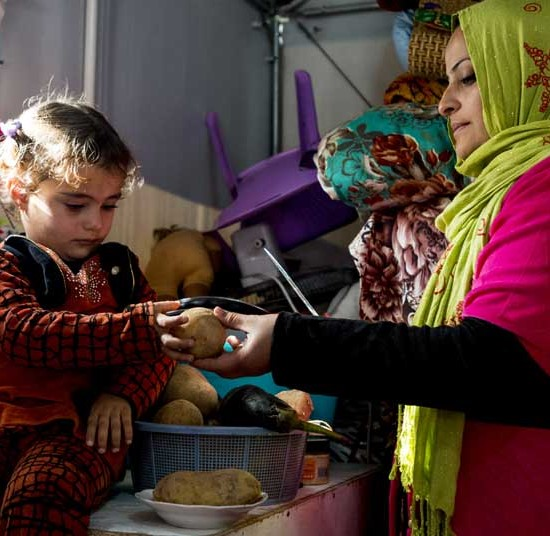 Hind and her five-year-old daughter in their new refugee housing in Al Jamea'a camp, Baghdad